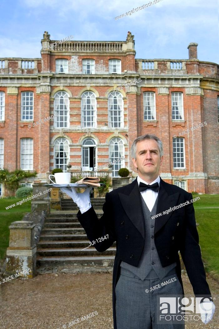 Stock Photo: Mature butler with tray of tea by manor house, low angle view.