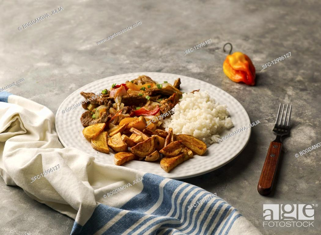 Stock Photo: Lomo saltado - Peruvian beef tenderloin with red onions, yellow chili, tomatoes, with potato fries and rice.