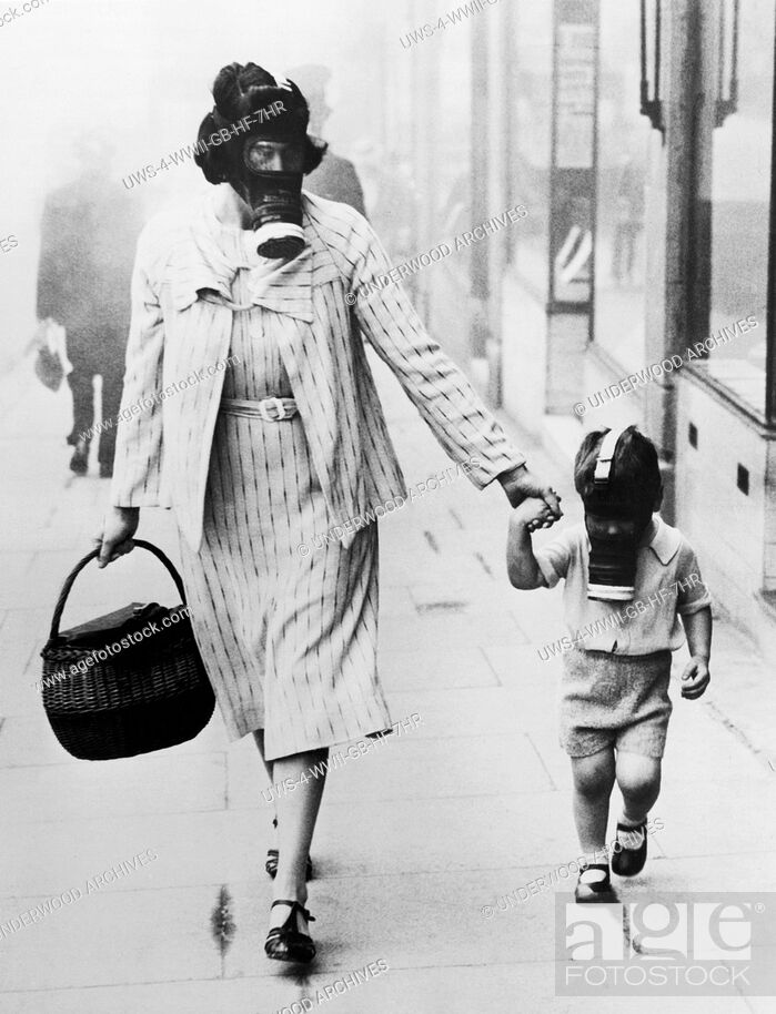 Stock Photo: London, England: September 12, 1941.A woman shopper and her child wearing gas masks pass through a gas drill area in Wembley.