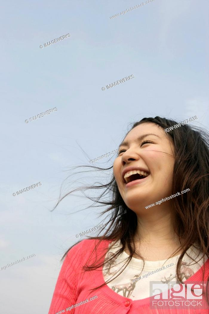 Stock Photo: A young woman is seen under the sky as she laughs her way to glory.