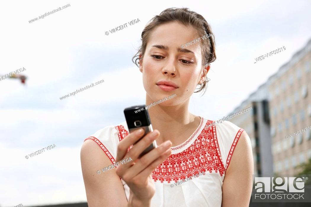 Stock Photo: Germany, Berlin, Young woman holding mobile phone, portrait, close-up.