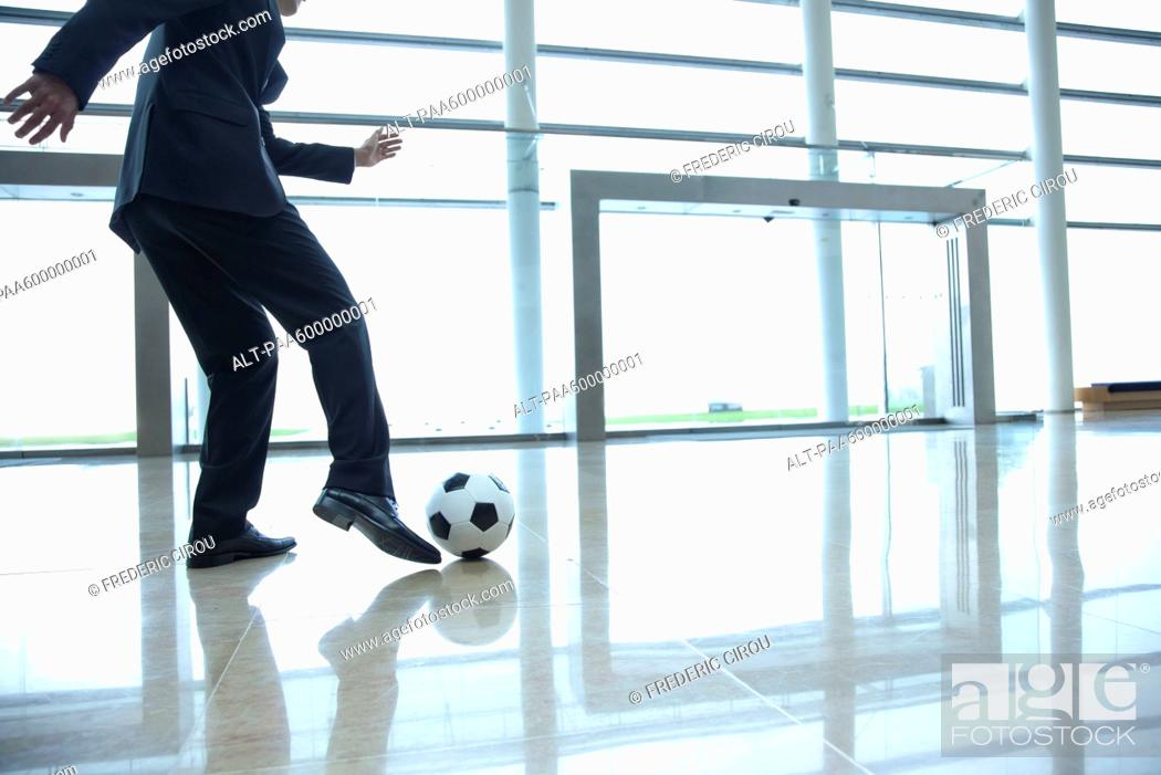 Stock Photo: Businessman kicking soccer ball in lobby.