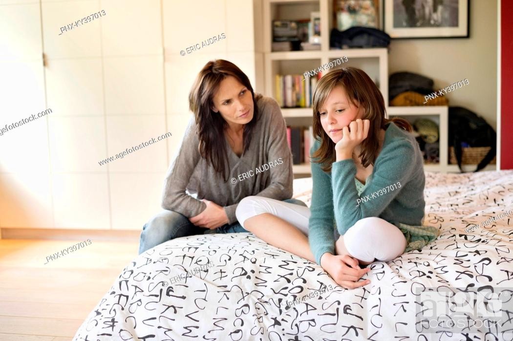 Stock Photo: Woman looking at her sad daughter in the bedroom.