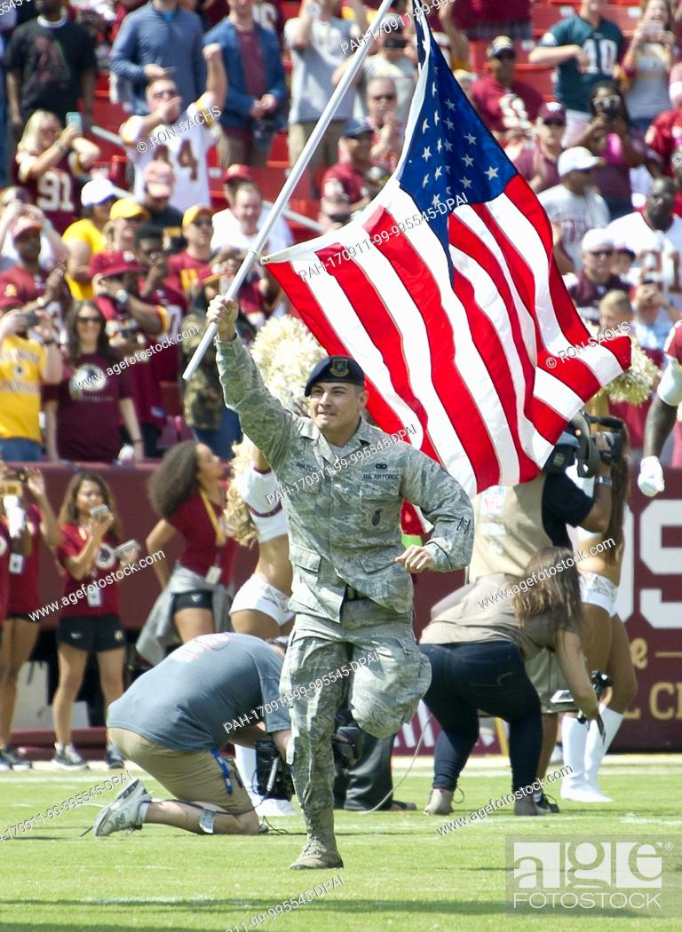 Imagen: A member of the United States Air Force runs onto the field carrying the American Flag prior to the Philadelphia Eagles against the Washington Redskins game at.