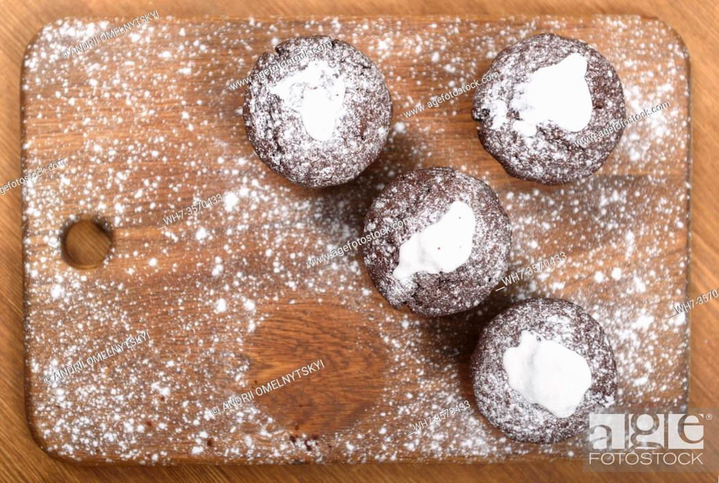 Imagen: chocolate muffins with white icing lying on a Board sprinkled with powdered sugar.