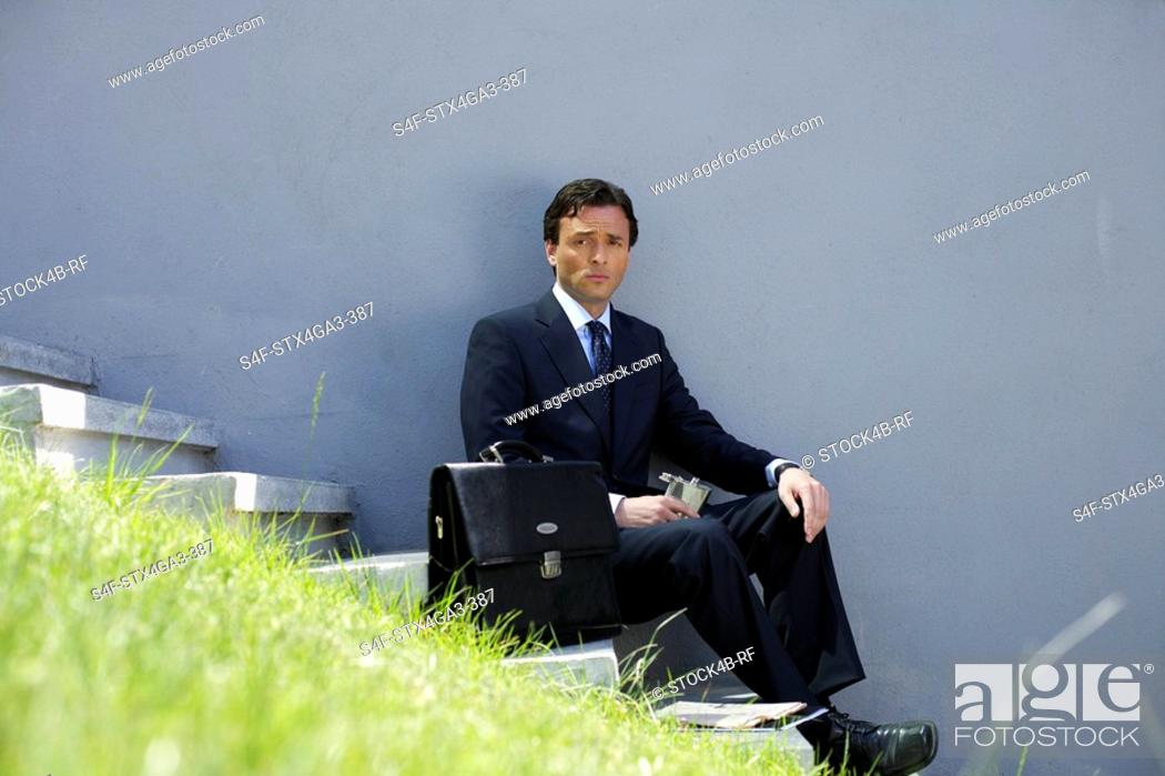 Stock Photo: Businessman sitting on a stairway.