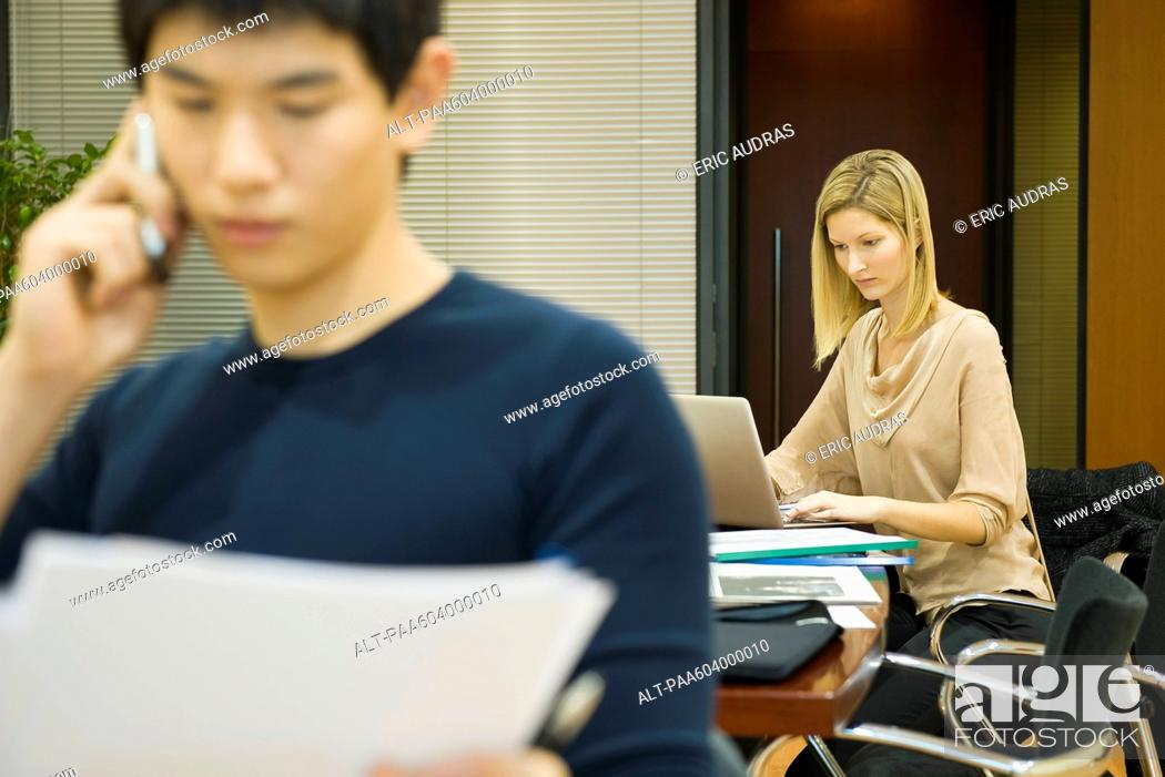 Stock Photo: Female executive working on laptop computer, colleague in foreground.