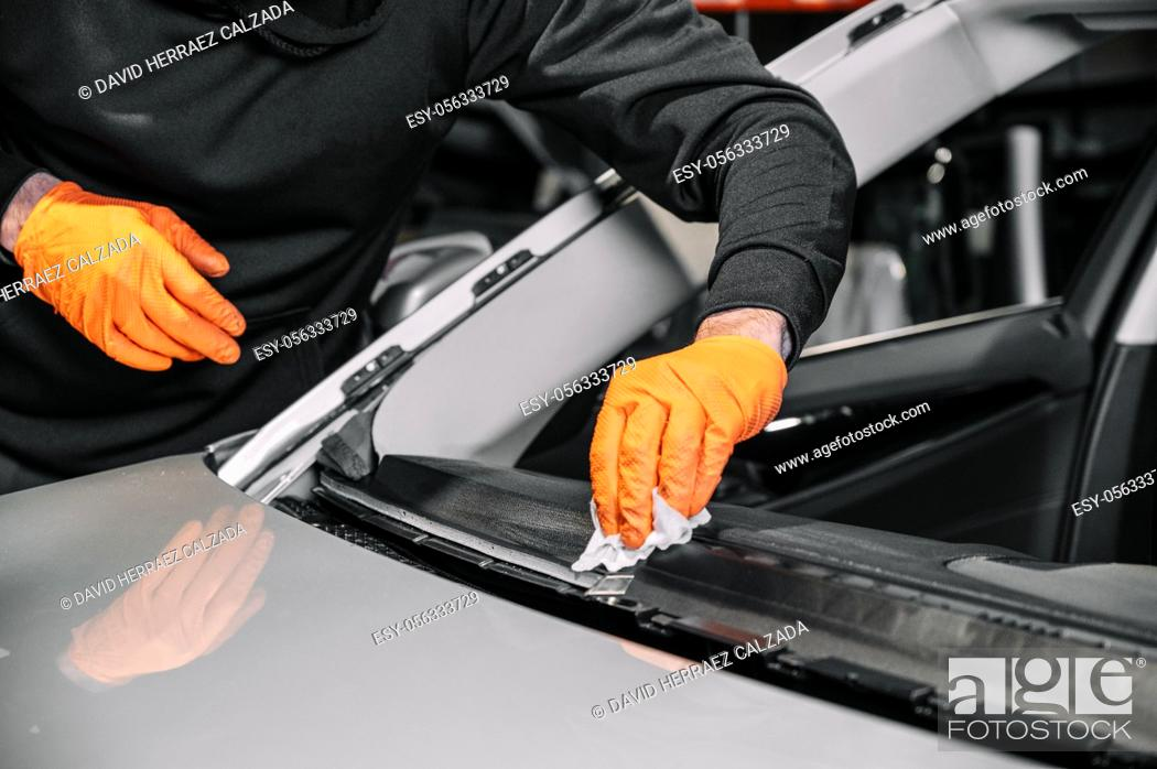 Stock Photo: Close up, Car glazing, fixing and repairing a windshield. Windscreen replace process of a car at a garage service. Cleaning a dashboard.