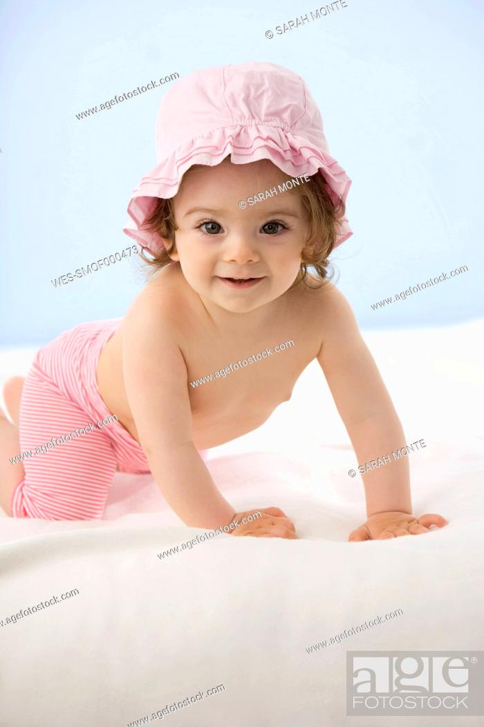 Stock Photo: Baby girl crawling on blanket, smiling.