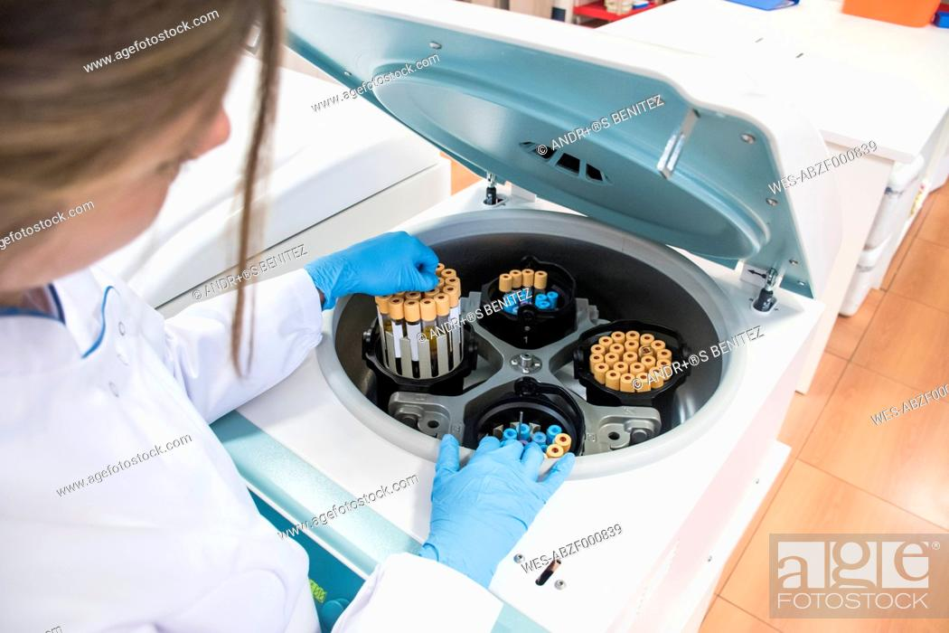 Stock Photo: Laboratory technician in analytical laboratory taking test tubes out of centrifuge.