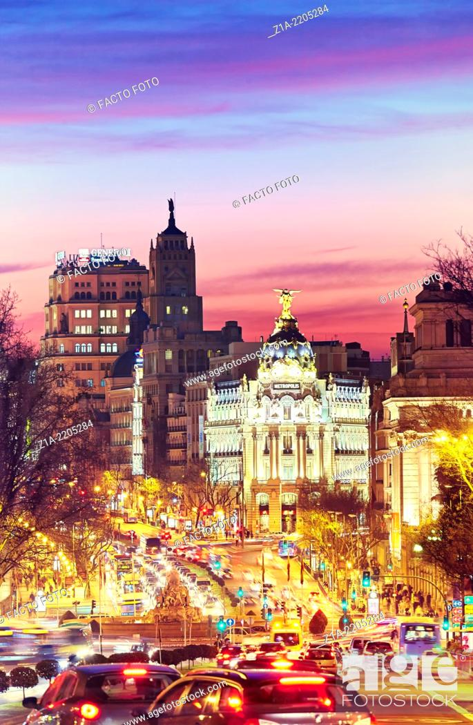 """Stock Photo: Metropolis building seen from """"""""Puerta de Alcala"""""""" monument by sunset. Madrid, Spain."""
