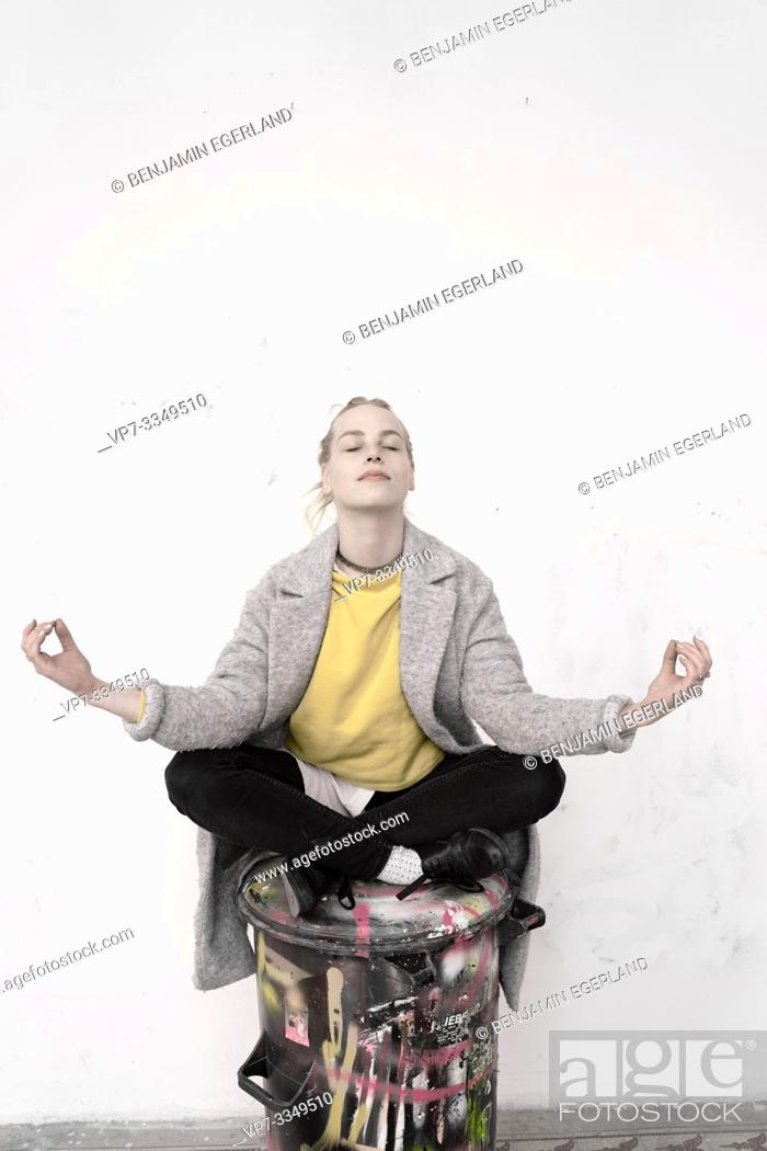 Stock Photo: young woman meditating on trash can with creative painting, in Germany.
