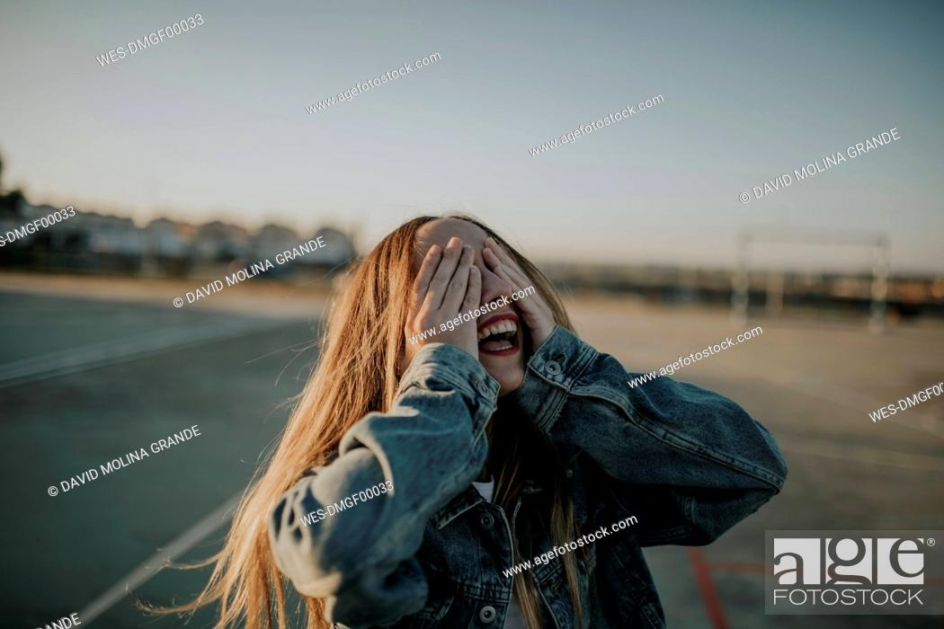 Stock Photo: Cheerful young woman covering her eyes outdoors.