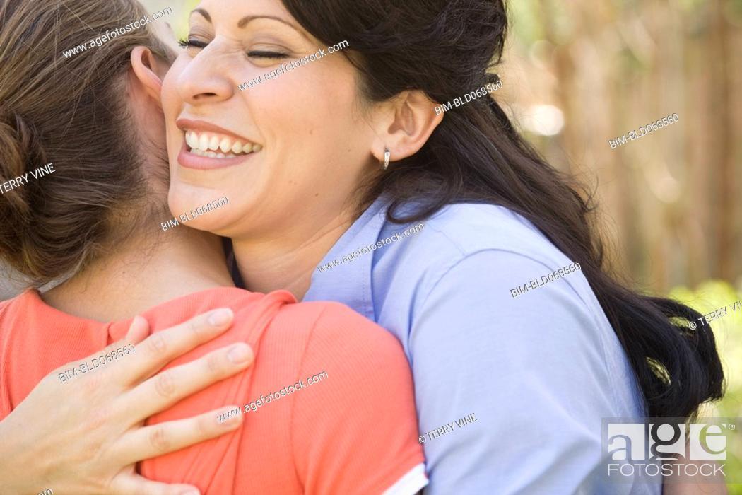 Stock Photo: Hispanic mother hugging daughter.
