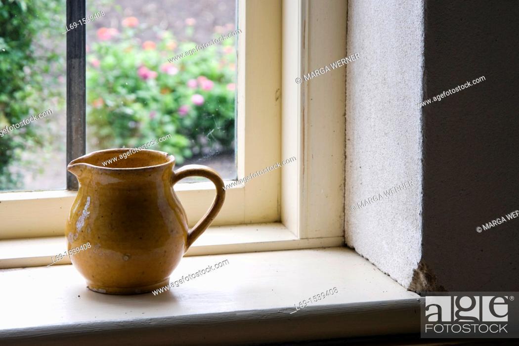 Stock Photo: Milk pot on the windowsill of an old house.