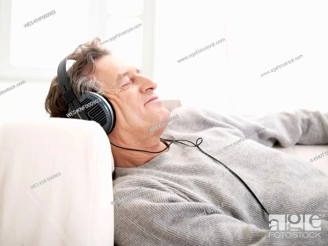 Stock Photo: Germany, Hamburg, Senior man listening music with eyes closed.