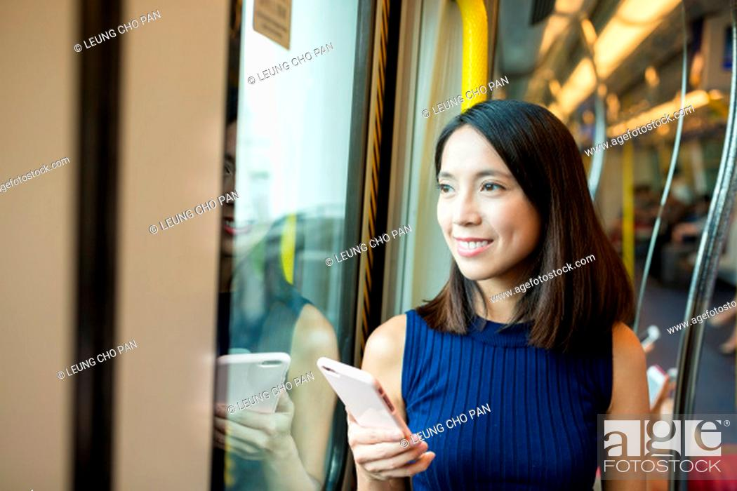 Stock Photo: Woman using mobile phone in metro compartment of Hong Kong.