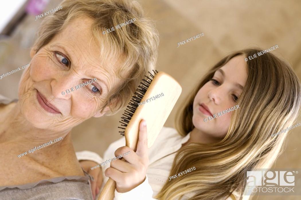 Stock Photo: Little girl brushing senior woman's hair, indoors.