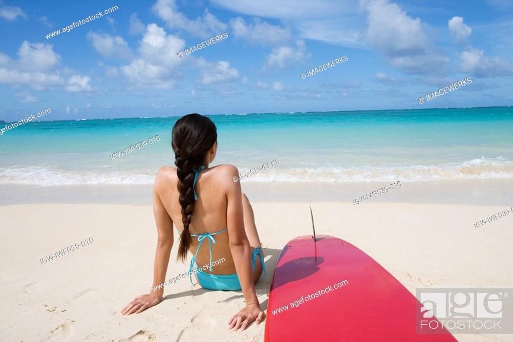 Stock Photo: A woman sitting on beach with surfboard.