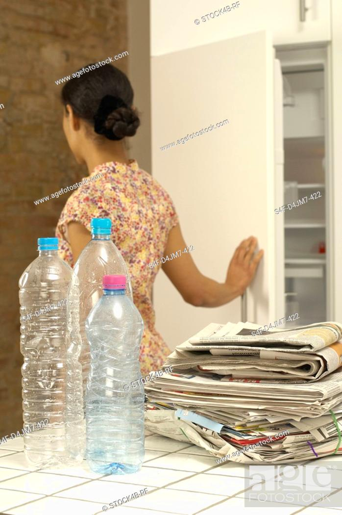 Stock Photo: Woman in kitchen with plastic bottles and old newspapers.