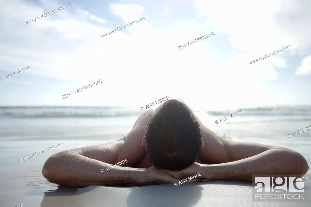 Stock Photo: Young man lying on beach, hands behind head.