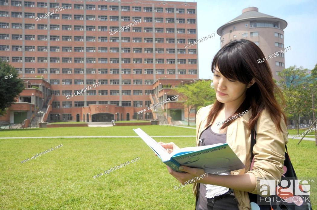 Stock Photo: Female university student reading a book.