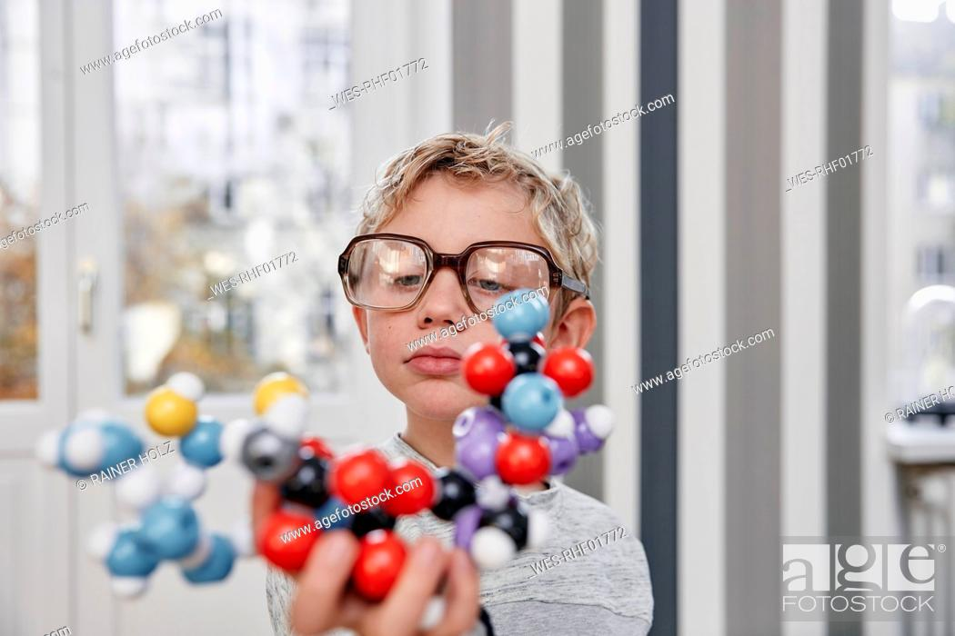 Stock Photo: Boy wearing oversized glasses looking at molecular model.