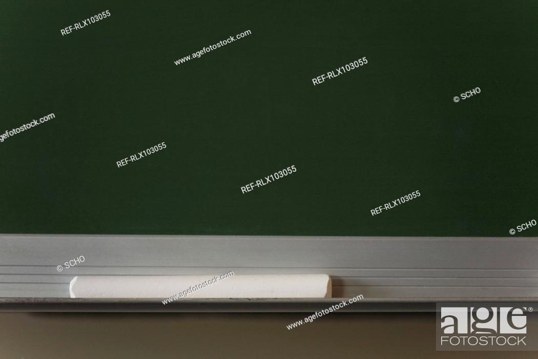 Stock Photo: White piece of chalk lying under black board, close-up.
