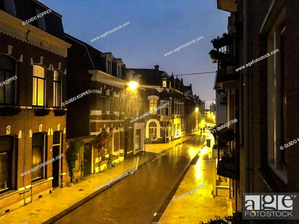 Stock Photo: Tilburg, Netherlands. Residential, down town street by Night and Rain with Thinder.