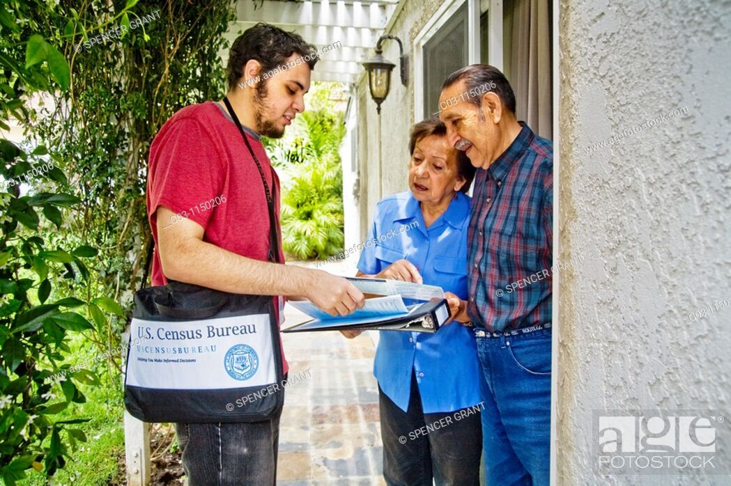 Stock Photo: Carrying his official shoulder bag, a 2010 U.S. Census enumerator shows his ID card while interviewing a Hispanic married couple in Southern California.