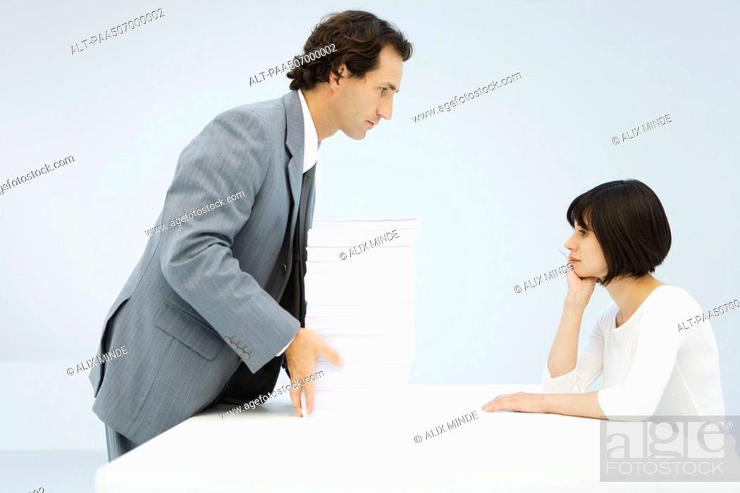 Stock Photo: Businessman sliding tall stack of paper across a table to woman leaning on her elbow.