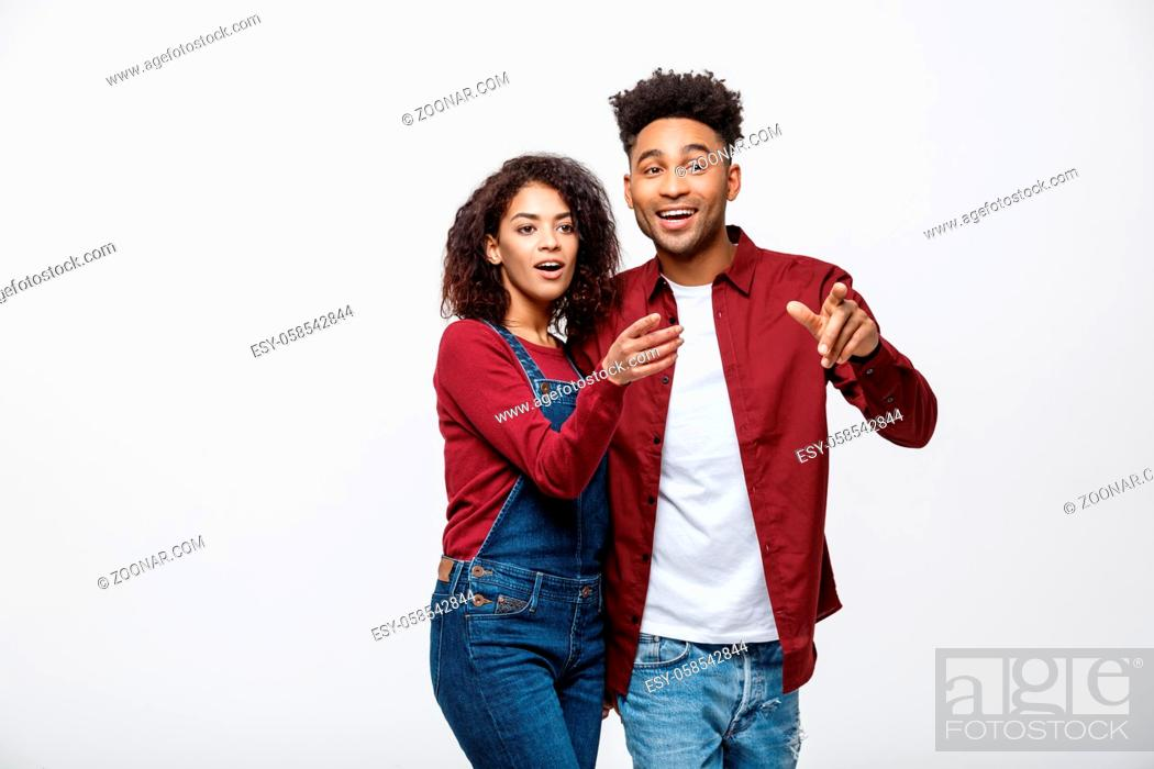 Stock Photo: Young African American people in casual clothes looking away and point finger. isolated on white background.