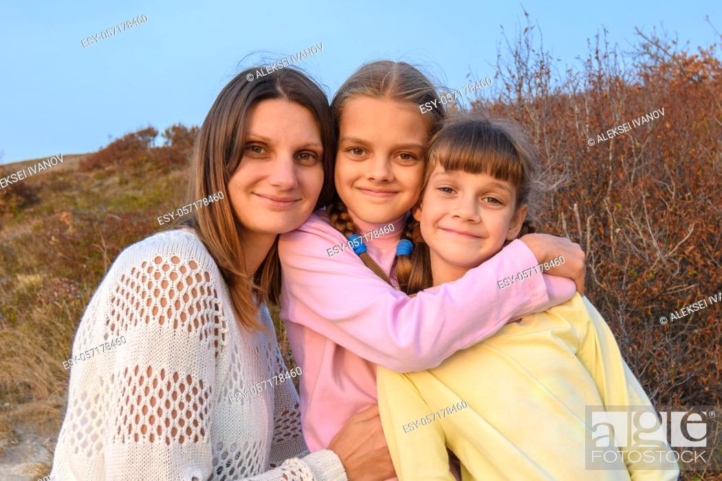 Stock Photo: Portrait of a happy girl with two daughters on the background of nature.