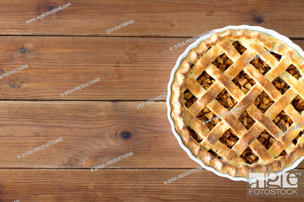 Stock Photo: close up of apple pie in mold on wooden table.