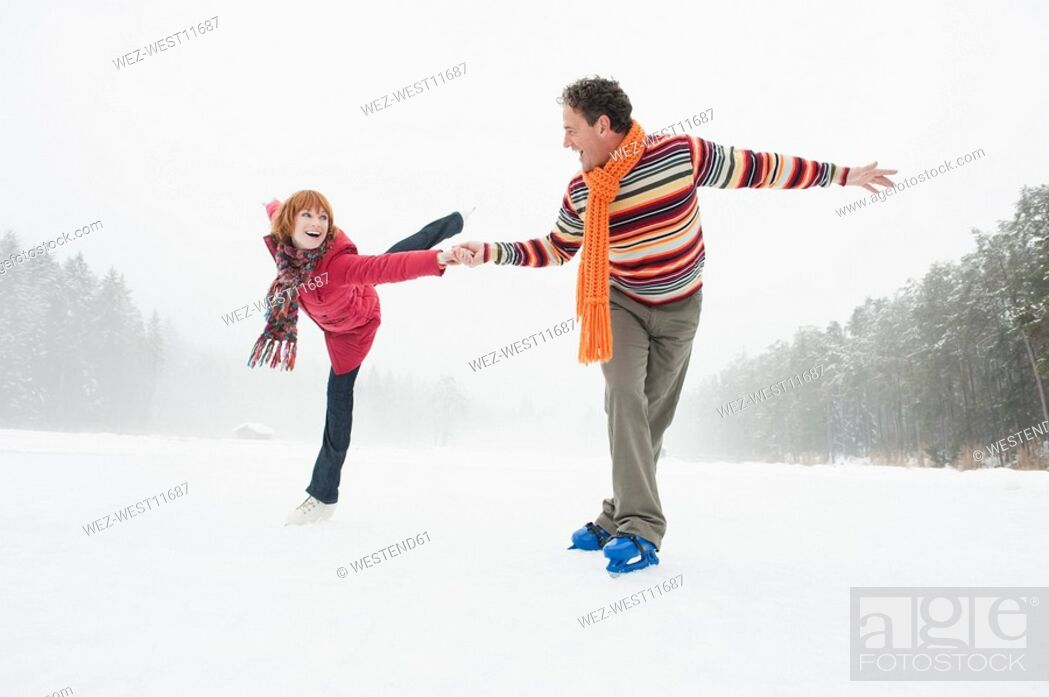 Stock Photo: Italy, South Tyrol, Seiseralm, Woman ice skating on one leg, Man assisting.