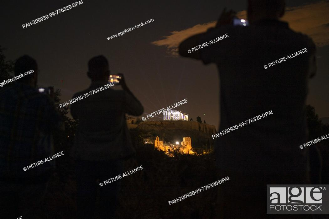 Imagen: 30 September 2020, Greece, Athen: People film and photograph the Acropolis with their mobile phones as it appears in a new light: a new lighting system was.