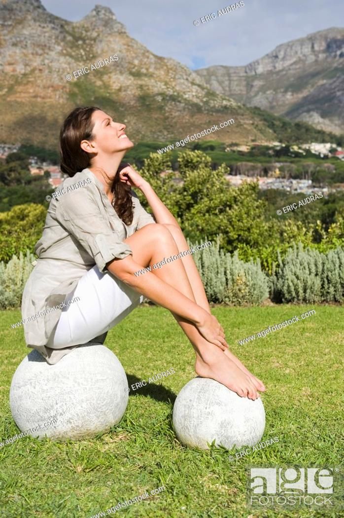 Stock Photo: Woman sitting on round stones and smiling.
