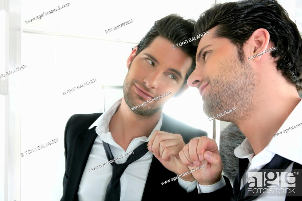 Photo de stock: Handsome narcissistic suit proud young man looking himself in the mirror.
