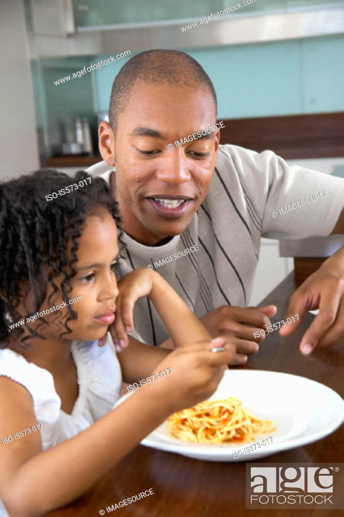 Stock Photo: Father and daughter at dining table.