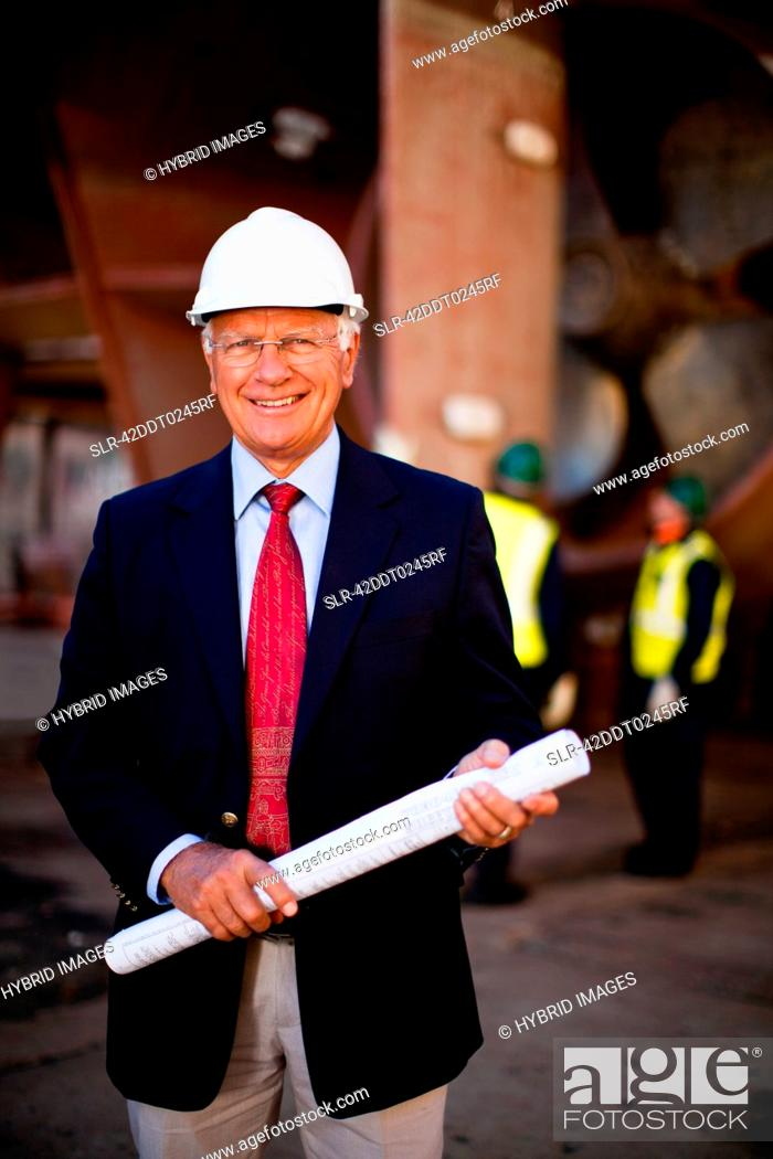 Stock Photo: Businessman with blueprints on dry dock.