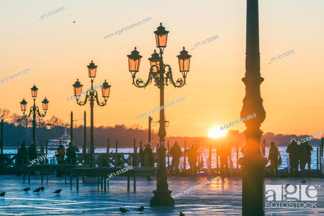 Stock Photo: St Mark's square, Venice, Veneto, Italy. Tourists admiring the sunrise over St. Mark's waterfront.