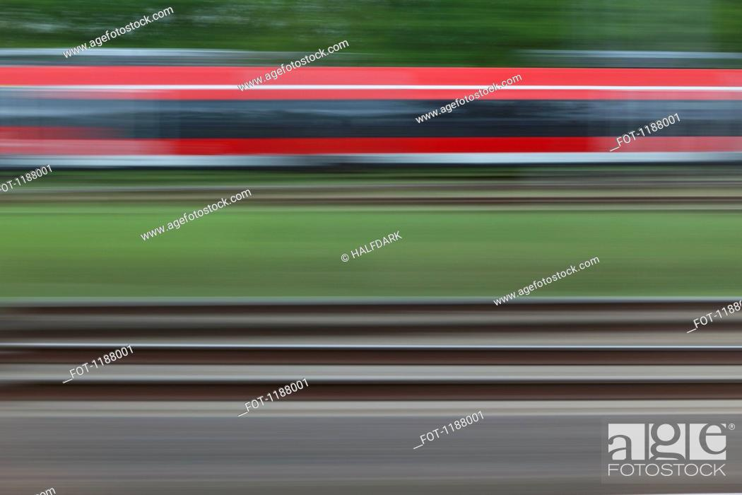 Stock Photo: Railroad tracks and a train, blurred motion, viewed from a moving train.