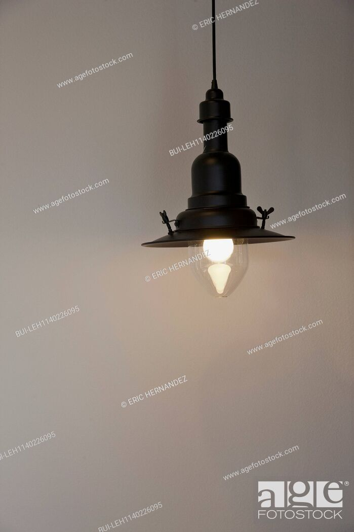 Stock Photo: Close-up of a lit hanging light against the wall.