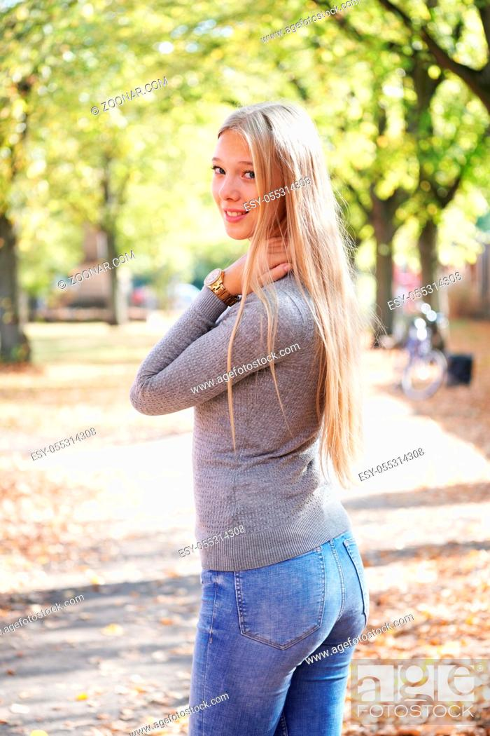 Photo de stock: teenage girl enjoying sunny day in park - rear view of young woman wearing jeans and sweater turning head around.