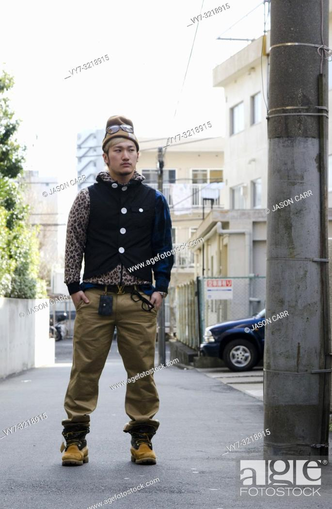 Stock Photo: Asian male model poses for pictures in the street.