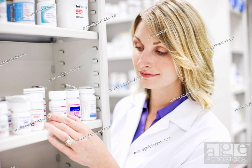 Stock Photo: Close up of pharmacist looking at pill bottles on shelf.