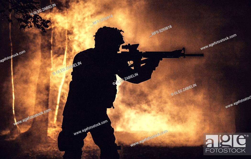 Stock Photo: Black silhouette of soldier in the smoke moving in battle operation. Back light, cropped, toned and colorized.