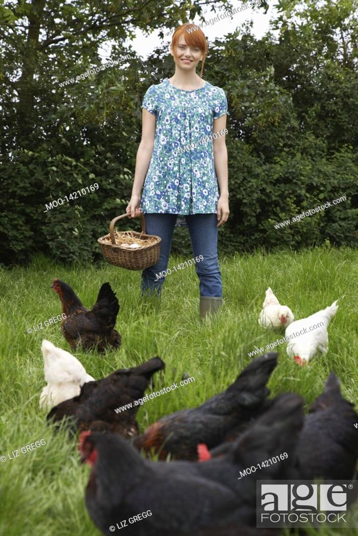 Stock Photo: Woman holding egg basket by hens in garden portrait.