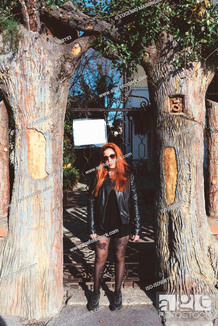 Stock Photo: Portrait of red haired woman wearing sunglasses standing between trees.