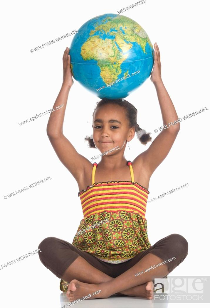 Stock Photo: African girl 6-7 with globe on head, portrait.